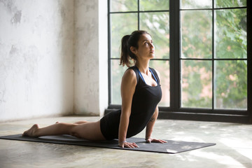 Young attractive woman practicing yoga at home, stretching in Urdhva mukha shvanasana exercise, upward facing dog pose, working out, wearing sportswear, black shorts, top, indoor full length, studio