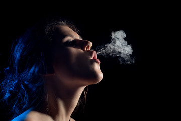 beautiful young woman smoking on black background with copy space