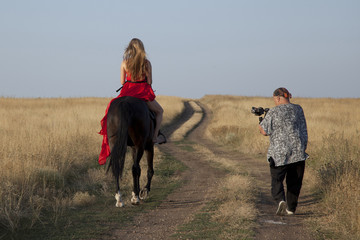 Cameraman shoots young woman on horseback