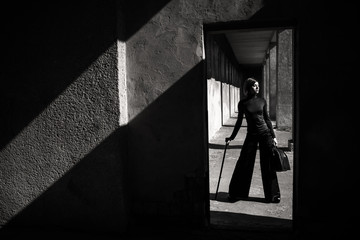 Fashion art portrait of elegant girl in geometric. Black and white photo of stylish young woman in cityscape