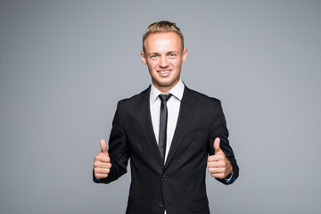 Portrait of excited man with opened mouth dressed in formal wear giving thumbs-up against gray