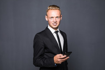 Happy business man in black suit typing sms on smartphone on grey