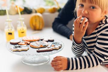 Girl eating Halloween cookie