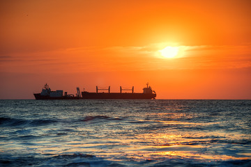 Sun setting at the sea with sailing cargo ship, sunrise view