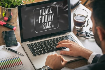 Black Friday sale text on a laptop screen, office background