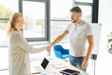 Positive delighted people shaking hands