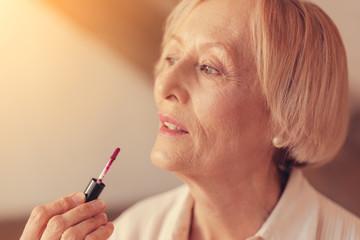 Close up of aged woman applying lip gloss
