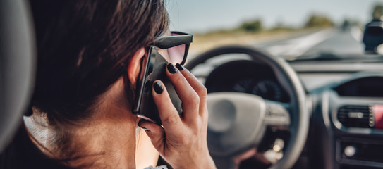 Woman driving car and talking on smart phone