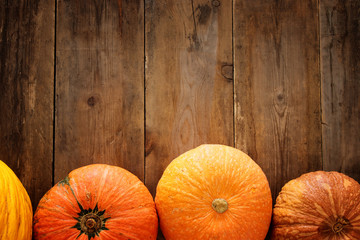 Pumpkins on wooden background. thanksgiving and halloween concept. Top view