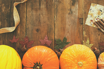 Pumpkins and autumn leaves on wooden background. thanksgiving and halloween concept. Top view
