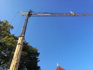 Moderner gelber Baukran mit Hydraulik vor strahlend blauem Himmel in Oerlinghausen bei Bielefeld  in Ostwestfalen-Lippe