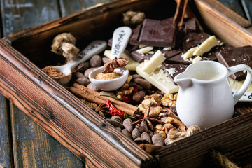 Ingredients for cooking hot chocolate. White and dark chopping chocolate, cocoa powder, cocoa beans, cream, cinnamon, sugar in spoons in wood tray over old wooden background. Close up