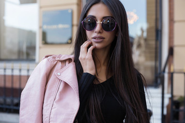 Fashion long hair woman with black shirt and hold pink leather jacket at city street. Stylish young model girl in elegant clothes outdoors. Lady with bright makeup.Fashion street style.