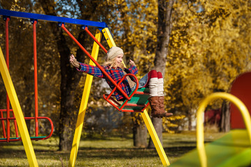 A young girl in coat is riding on a swing at playground. Autumn park