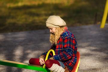 Sadness girl on children playground