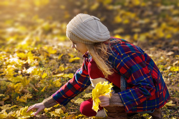 Young girl in coat and beret collects autumn leaves in the park