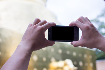 Close up.Asian young man hand holing mobile phones take photos location and nature views, With blank copy space for your text message,Selective focus.Isolated white background