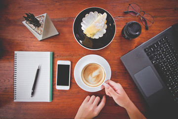 Top view Office desk with laptop,supplies and hand holding hot coffee drinking,DSLR camera,Lens,Cactus,Mobile phone Black space on wood,Vintage tone