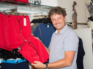 handsome man store clothes manager present clothing to customers
