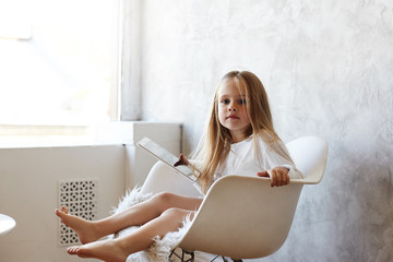 Picture of cute little girl familiar with gadgets sitting barefooted on comfortable armchair by the window, holding digital tablet, using free wifi, watching video online on how to bake cookies
