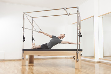 Pilates instructor performing exercise on cadillac equipment