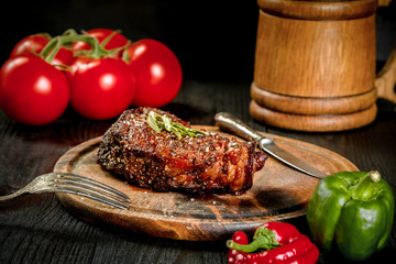 Grilled steak seasoned with spices and fresh herbs served on a wooden board with wooden mug of beer, fresh tomato, red and green peppers