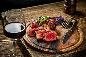 Tuinposter Steakhouse Grilled ribeye beef steak with red wine, herbs and spices on wooden table