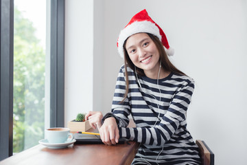 Asian girl smiling sitting in coffee shop,Woman wearing Santa Claus hat,Teens are listening to music from headphones.