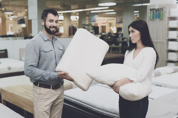 A couple in a large store of beds and mattresses chooses pillows. They examine several variants of pillows