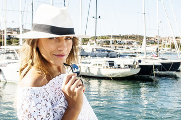 Portrait of beautiful smiling young woman in white hat walking in harbor