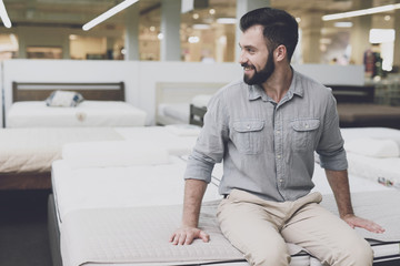 A man in a large store chooses a mattress for himself. He sat down on him to try it out