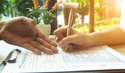 The human hand with pen is signing on The Insurance Claim Form,on wooden desk,vintage tone.