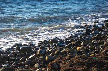 rocky sea shore with pebble beach, waves with foam