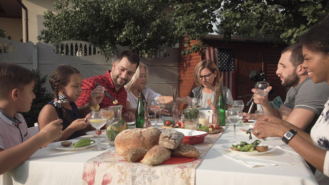 Middle angle of cheerful big family sitting and eating in the garden during reunion party.
