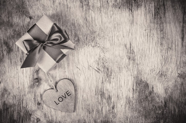 Present for the day of lovers. Gift box and wooden heart. St. Valentine's Day. Monochrome