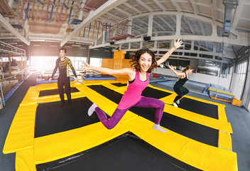 Cheerful and happy woman practicing and jumping on trampolines in a sports indoor center, workout and modern entertainment concept