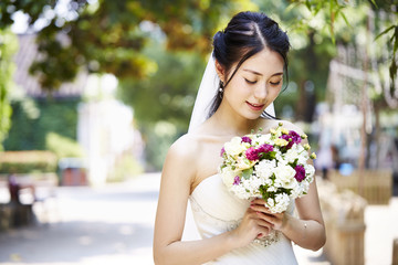 outdoor portrait of happy asian bride with flowers