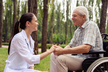 Doctor holding a smiling old man's hand