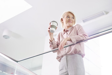 Cheerful businesswoman with mug of coffee leaning on a railing