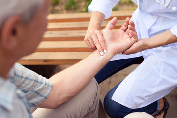 The doctor measure the patient's pulse while sitting on a bench in the park