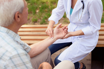 Doctor measures the patient's pulse while sitting in the park