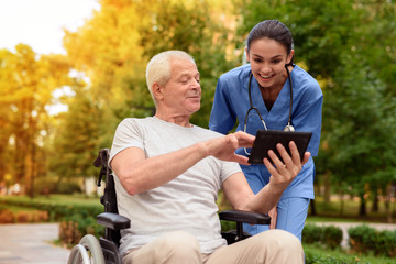 An old man in a wheelchair proudly shows a happy nurse something in his tablet