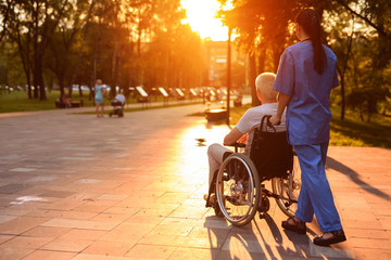 A nurse and an old man who sits in a wheelchair strolling in the park at sunset