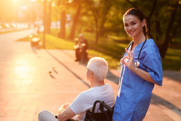 The nurse shows the gesture all OK. Behind her is an old man in a wheelchair