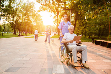A nurse is standing behind an old man, who is sitting in a wheelchair and reading a book at sunset