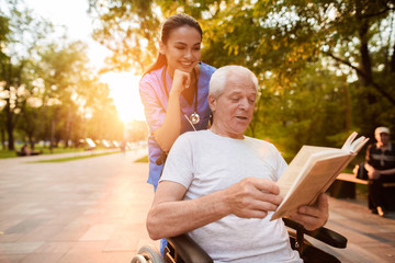 The old man who is sitting in a wheelchair is reading a book. A nurse behind the old man and also looking at the book