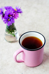 A pink mug of black tea on a light background and purple flowers.