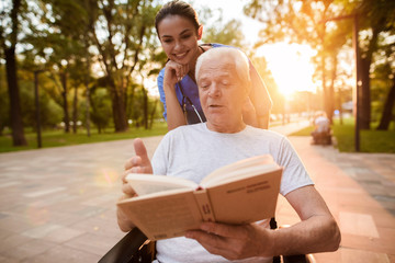 A nurse watches as the old man reads a book in the park at sunset