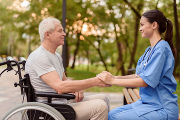 An old man who sits in a wheelchair and a nurse who sits next to the bench holding hands