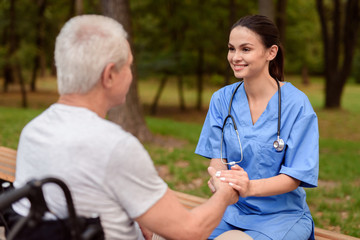 A nurse is smiling and holding the hand of an old man who is sitting next to in a wheelchair in the park